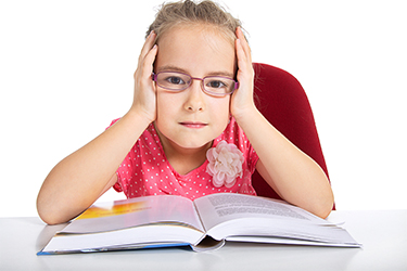 girl wearing glasses reading a book